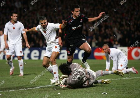 Fred of Olympique Lyonnais hurdles Alexander Doni of AS Roma