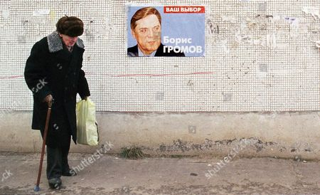 An Elderly Man Walks at the Wall with the Lonely Poster of Boris Gromov Former Chief of Russian Troops in Aghanistan Now the Member of 'Fatherland-all Russia' Electoral Block Moscow Russia 17 December 1999 the Parliamential Elections in Russia Are Scheduled on Sunday Russian Federation Moscow