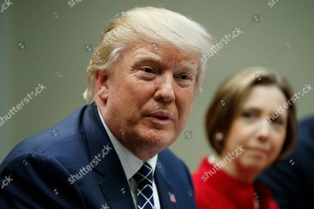 Cape Cod Five Cents Savings Bank CEO Dorothy Savarese listens at right as President Donald Trump meets with leaders from small community banks, in the Roosevelt Room of the White House in Washington