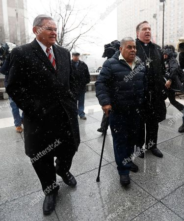 Catalino Guerrero, center, walks with U.S. Senator Bob Menendez, left, and Newark Archbishop Cardinal Joseph Tobin, right, during a rally outside of the Newark immigration building before attending an immigration hearing, in Newark, N.J. Guerrero, who arrived in the U.S. illegally in 1991, is facing deportation. Organizers claim he is an upstanding citizen and should not be deported