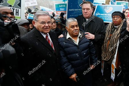 Catalino Guerrero, center, stands with U.S. Senator Bob Menendez, left, and Newark Archbishop Cardinal Joseph Tobin during a rally outside of the Newark immigration building before attending an immigration hearing, in Newark, N.J. Guerrero, who arrived in the U.S. illegally in 1991, is facing deportation. Organizers claim he is an upstanding citizen and should not be deported