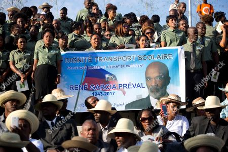 School transportation workers hold up a banner featuring former President Rene Preval, during his funeral service, in Port-au-Prince, Haiti, . Thousands of people from around Haiti gathered at a city park Saturday for Preval's state funeral capping six days of mourning for the man who led the country during a devastating January 2010 earthquake and its chaotic aftermath