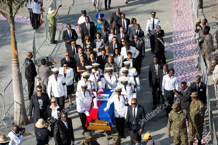 Police officers and family members accompany the coffin containing the remains of former President Rene Preval during his funeral service in Port-au-Prince, Haiti, . Thousands of people from around Haiti gathered at a city park Saturday for Preval's state funeral capping six days of mourning for the man who led the country during a devastating January 2010 earthquake and its chaotic aftermath