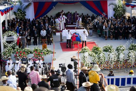 Police officers stand vigil over the coffin containing the remains of former President Rene Preval during funeral services in Port-au-Prince, Haiti, . Thousands of people from around Haiti gathered at a city park Saturday for Preval's state funeral capping six days of mourning for the man who led the country during a devastating January 2010 earthquake and its chaotic aftermath
