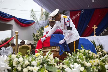 A police officer adjusts a flag draped over the coffin containing the remains of former President Rene Preval during his funeral service in Port-au-Prince, Haiti, . Thousands of people from around Haiti gathered at a city park Saturday for Preval's state funeral capping six days of mourning for the man who led the country during a devastating January 2010 earthquake and its chaotic aftermath