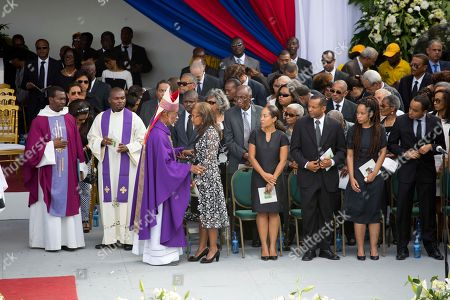 Stock Photo of Elisabeth Debrosse Preval, Joseph Lafontant Former first lady Elisabeth Debrosse Preval, center, talks with Bishop Joseph Lafontant, as family members watch, from left center to right; Dominique Preval Georges, Alex Georges, Patricia Preval, and Karl Delatour, during the late leader's funeral service in Port-au-Prince, Haiti, . Thousands of people from around Haiti gathered at a city park Saturday for Preval's state funeral capping six days of mourning for the man who led the country during a devastating January 2010 earthquake and its chaotic aftermath