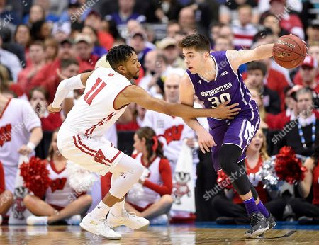 Northwestern guard Bryant McIntosh (30) dribbles against Wisconsin guard Jordan Hill (11) during the first half of an NCAA college basketball game in the Big Ten tournament, in Washington. Wisconsin won 76-48