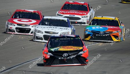 Martin Truex Jr. (78) leads Kyle Larson (42) Jamie McMurray (1) Ryan Blaney (21) and Kyle Busch (18) as they head into pit lane during the NASCAR Cup Series auto race, at Las Vegas Motor Speedway in Las Vegas