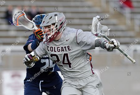 Colgate Raiders midfielder Robby Dunigan #24 dodges to the goal against the defense of Hobart Statesmen midfielder Kevin Murphy #25 during the first quarter of the game on Wednesday, March, 8, at Andy Kerr Stadium in Hamilton, New York. Colgate defeated Hobart 13-6