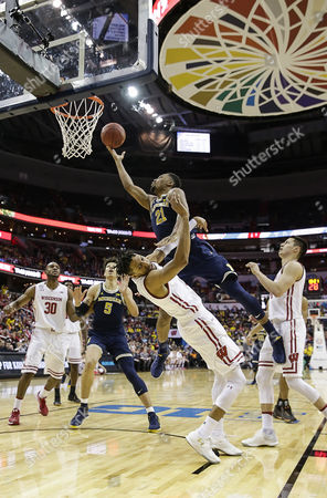 Michigan Wolverines G/F #21 Zak Irvin runs over Wisconsin Badgers G #11 Jordan Hill on his way to the hoop during the Big 10 Men's Basketball Tournament championship game between the Wisconsin Badgers and the Michigan Wolverines at the Verizon Center in Washington D.C.. Michigan wins the Big Ten Tournament defeating Wisconsin, 71-56