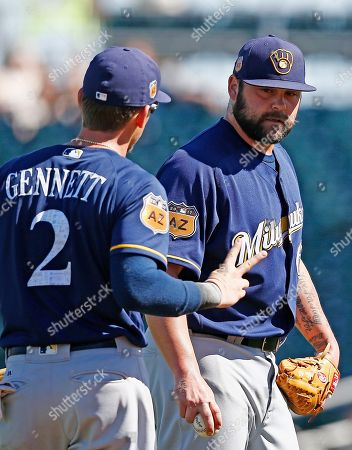 Milwaukee Brewers second baseman Scooter Gennett (2) holds up two fingers to see how well pitcher Joba Chamberlain, right, can see after Chamberlain lost an infield high hop ground ball hit by Cincinnati Reds' Stuart Turner in the sun for an infield hit during the fourth inning of a spring training baseball game, in Goodyear, Ariz