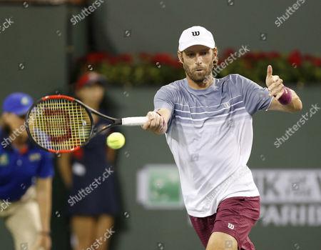 Stephane Robert of France returns a shot against Roger Federer of Switzerland during the BNP Paribas Open at Indian Wells Tennis Garden in Indian Wells, California