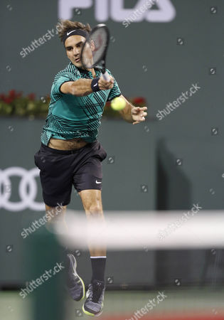Roger Federer of Switzerland hits a shot against Stephane Robert of France during the BNP Paribas Open at Indian Wells Tennis Garden in Indian Wells, California