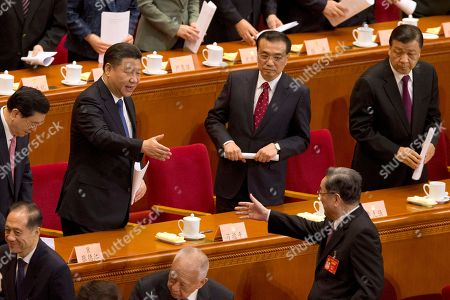 Chinese President Xi Jinping reaches out to shake hands with Yu Zhengsheng, Chairman of the Chinese People's Political Consultative Conference (CPPCC), lower right, during the closing session of the CPPCC at Beijing's Great Hall of the People on