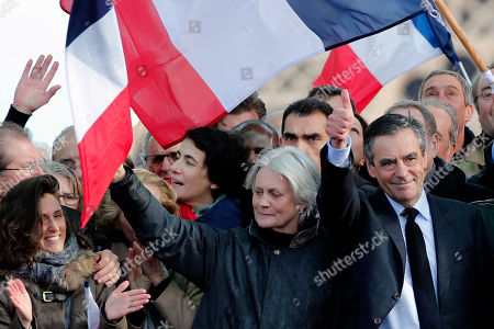 """French conservative presidential candidate Francois Fillon, right, thumbs up with his wife Penelope after delivering his speech during a rally in Paris, . Fillon is urging his supporters not to """"give up the fight"""" for the presidency despite corruption allegations dogging him. At left is their daughter Marie Fillon"""