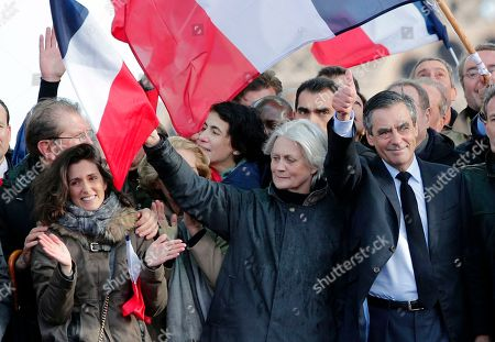 """French conservative presidential candidate Francois Fillon, right, his wife Penelope, center, and his daughter Marie, left, appear during a rally in Paris, . Fillon is urging his supporters not to """"give up the fight"""" for the presidency despite corruption allegations dogging him"""