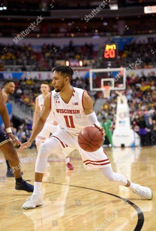 Wisconsin guard Jordan Hill (11) dribbles during the first half of the Big Ten NCAA college basketball championship game against Michigan, in Washington