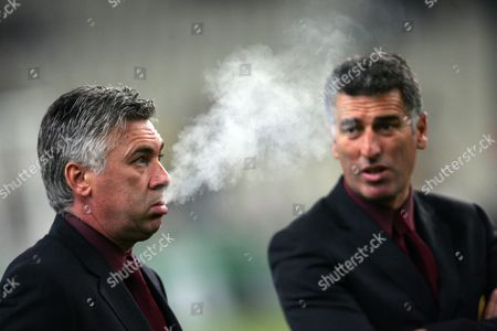 AC Milan manager Carlo Ancelotti exhales his cigarette smoke as his assistant Mauro Tassotti looks on