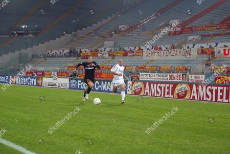 Real Madrid's Roberto Carlos and Roma's Gaetano D'Agostino chase the ball in an empty Stadio Olympico. Fans were banned after the referee was hit by a missle during a previous Champion's League match.