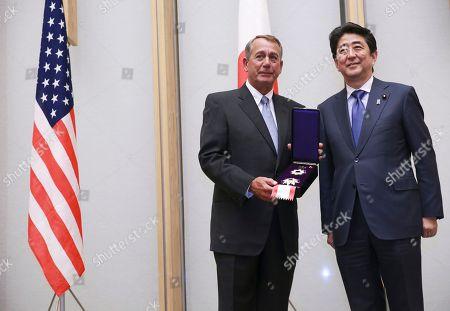 John Boehner, Shinzo Abe Former U.S. House Speaker John Boehner, left, holds a decoration medal flanked by Japanese Prime Minister Shinzo Abe, right, during the award ceremony at the prime minister's office in Tokyo