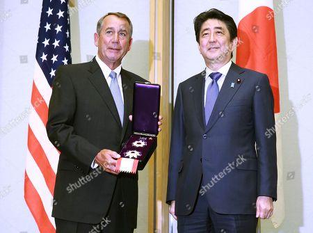 John Boehner, Shinzo Abe Former U.S. House Speaker John Boehner, left, holds a decoration medal flanked by Japanese Prime Minister Shinzo Abe during the award ceremony at the prime minister's office in Tokyo