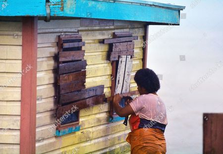 Fijian woman boarding up her house during a Tropical Cyclone. On Feb 2016 Severe Tropical Cyclone Winston was the strongest tropical cyclone in Fiji in recorded history.