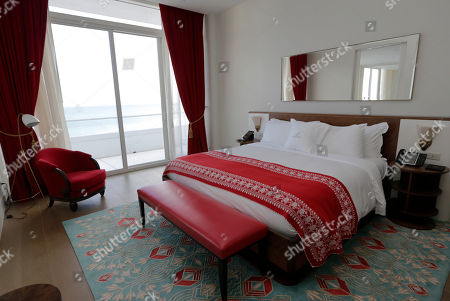 An oceanfront room in a two-bedroom suite with the signature red and teal blue color scheme is shown in the Faena Hotel in Miami Beach, Fla. The beachfront hotel is the flagship of Faena District, a cluster of buildings developed by Argentine hotel magnate Alan Faena where decaying structures and empty parking lots are giving way to opulent hotels, condos, and a performing arts center