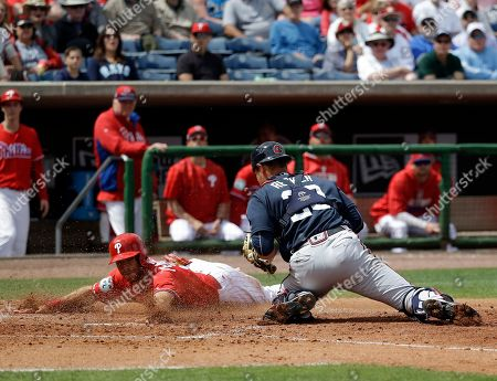 Stock Picture of Taylor Featherston, Anthony Recker Philadelphia Phillies' Taylor Featherston, left, slides past Atlanta Braves catcher Anthony Recker to score a run in the fifth inning in a spring training baseball game, in Clearwater, Fla