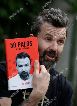 "Spanish singer Pau Dones holds up a copy of his book, ""50 palos, y sigo sonando,"" Spanish for ""50 Years, and I'm Still Dreaming,"" during an interview in Mexico City, . Despite the return of his colon cancer, Dones will perform at Vive Latino on Saturday with his band Jarabe de Palo"