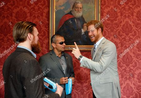 Britain's Prince Harry chats with US veteran Ivan Castro, center, and UK veteran Karl Hinett, left, who will run the Boston and London Marathons for the Heads Together Campaign, after he attended a conference at King's College in London,. Prince Harry attended the Veterans' Mental Health Conference where he led a panel discussion with three veterans on the benefits of having open conversations and getting the right support for a range of mental health issues