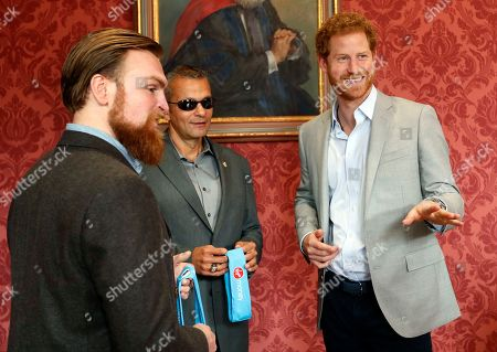 Stock Image of Britain's Prince Harry chats with US veteran Ivan Castro, centre, and UK veteran Karl Hinett, left, who will run the Boston and London Marathons for the Heads Together Campaign, after he attended a conference at King's College in London,. Prince Harry attended the Veterans' Mental Health Conference where he led a panel discussion with three veterans on the benefits of having open conversations and getting the right support for a range of mental health issues