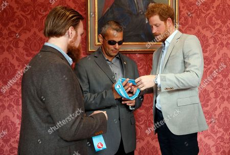 Britain's Prince Harry gives head bands to US veteran Ivan Castro, centre, and UK veteran Karl Hinett, left, who will run the Boston and London Marathons for the Heads Together Campaign, after he attended a conference at King's College in London,. Prince Harry attended the Veterans' Mental Health Conference where he led a panel discussion with three veterans on the benefits of having open conversations and getting the right support for a range of mental health issues