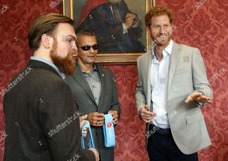 Stock Photo of Britain's Prince Harry chats with US veteran Ivan Castro, centre, and UK veteran Karl Hinett, left, who will run the Boston and London Marathons for the Heads Together Campaign, after he attended a conference at King's College in London