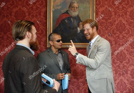 Britain's Prince Harry chats with US veteran Ivan Castro, center, and UK veteran Karl Hinett, left, who will run the Boston and London Marathons for the Heads Together Campaign, after he attended a conference at King's College in London