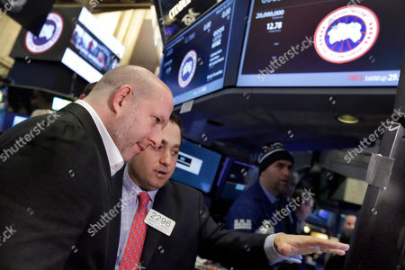 Canada Goose CEO & President Dani Reiss, left, listens to specialist Gennaro Saporito before his company's IPO begins trading on the floor of the New York Stock Exchange
