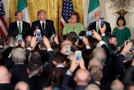 President Donald Trump speaks during a St. Patrick's Day reception in the East Room of the White House in Washington, as Irish Prime Minister Enda Kenny, left, his wife, Fionnuala Kenny, center, and Vice President Mike Pence and his wife Karen listen