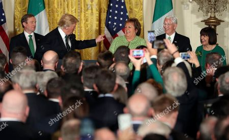 Stock Photo of President Donald Trump gestures to Fionnuala Kenny, wife of Irish Prime Minister Enda Kenny, left, during a St. Patrick's Day reception in the East Room of the White House in Washington, Vice President Mike Pence and his wife Karen watch