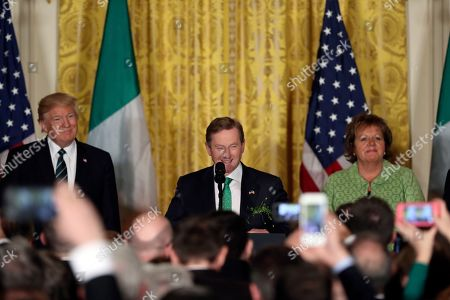 President Donald Trump, left, listens as Irish Prime Minister Enda Kenny speaks during a St. Patrick's Day reception in the East Room of the White House in Washington, as Fionnuala Kenny, right, watches