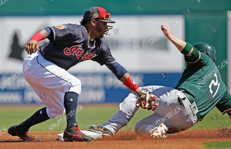 Oakland Athletics catcher Stephen Vogt (21) beats the tag at second base by Cleveland Indians second baseman Michael Martinez, left, for a double during the first inning of a spring training baseball game, in Goodyear, Ariz