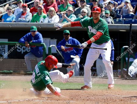 Michael Saunders, Cesar Hernandez Philadelphia Phillies' Michael Saunders, right, signals to Cesar Hernandez (16) as he slides home to score a run against the Toronto Blue Jays in the fifth inning of a spring training baseball game, in Clearwater, Fla