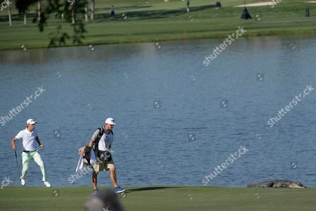 Smylie Kaufman, left, reacts as he spots an alligator lying on the sixth fairway next to a lake during the second round of the Arnold Palmer Invitational golf tournament in Orlando, Fla