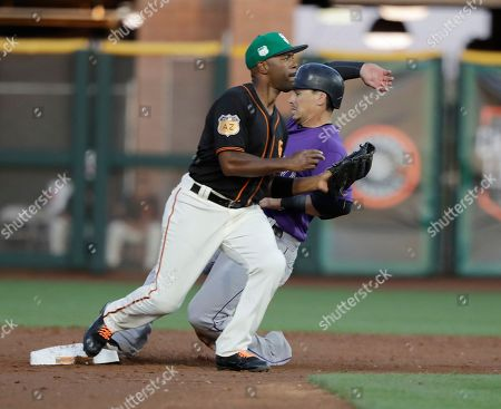 Colorado Rockies' Tony Wolters is forced out at second and San Francisco Giants' Jimmy Rollins throws to first for a double play during the second inning of a spring training baseball game, in Scottsdale, Ariz