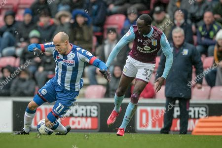 Gabriel Obertan (Wigan Athletic) is brought down by Albert Adomah (Aston Villa) during the EFL Sky Bet Championship match between Wigan Athletic and Aston Villa at the DW Stadium, Wigan