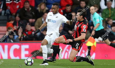 Jordan Ayew of Swansea City is tackled by Charlie Daniels of Bournemouth.