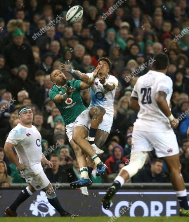 Ireland's Simon Zebo, second left, jumps for a lose ball with England's Anthony Watson during the Six Nations rugby union international match between Ireland and England at the Aviva stadium in Dublin, Ireland, . Ireland won the game 13-9, but England won the Six nations Championships