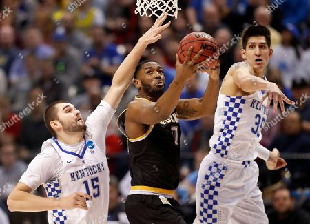Wichita State's Rashard Kelly, center, heads to the basket as Kentucky's Isaac Humphries (15) and Derek Willis (35) defend during the first half of a second-round game in the men's NCAA college basketball tournament, in Indianapolis