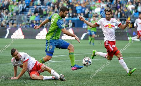 Seattle Sounders forward Will Bruin, center, cuts through New York Red Bulls' Aaron Long, left, and Damien Perrinelle, right, to make a shot on goal during the second half of an MLS soccer match, in Seattle. The Sounders won 3-1
