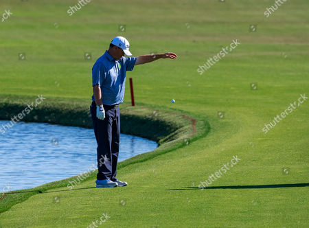 Orlando, Florida, USA-Greg Chalmers takes a drop on the 18th hole fairway during the final round of the Arnold Palmer Invitational