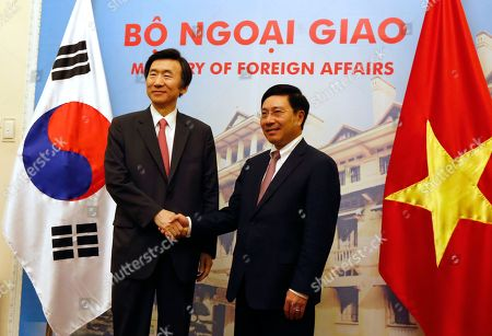 South Korean Foreign Minister Yun Byung-se, left, shakes hands with his Vietnamese counterpart Pham Binh Minh before their talk in Hanoi, Vietnam, . Yun is on a two-day visit to the Southeast Asian nation boost ties between the two countries