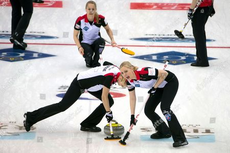 Switzerland's Nadine Lehmann, right sweeps a throw from Nicole Schwagli, top during a match against Canada at the CPT World Women's Curling Championship 2017 (WWCC) held in Beijing's Capital Gymnasium